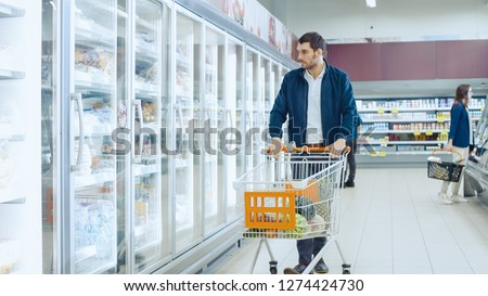 At the Supermarket: Handsome Man Pushes Shopping Card and Browses for Products in the Frozen Goods Section. Man Looks into Glass Door Fridge, Looking for Dairy Products. Other Customer Shopping