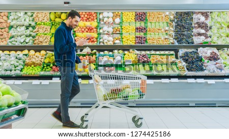 At the Supermarket: Handsome Man with Smartphone, Pushes Shopping Cart, Walks Past Fresh Produce Section of the Store. Man Immersed in Internet Surfing on His Mobile Phone.