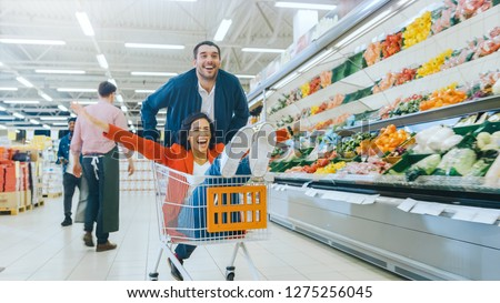 At the Supermarket: Man Pushes Shopping Cart with Woman Sitting in it, Happy Couple Has Fun Racing in a Trolley through the Fresh Produce Section of the Store. #1275256045
