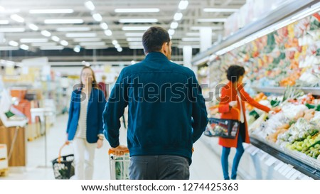 At the Supermarket: Man Pushing Shopping Cart Through Fresh Produce Section of the Store. Store with Many Customers Shopping. Following Back View Shot.