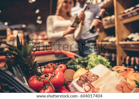 At the supermarket. Shopping cart full of goods, in the background young couple choosing wine