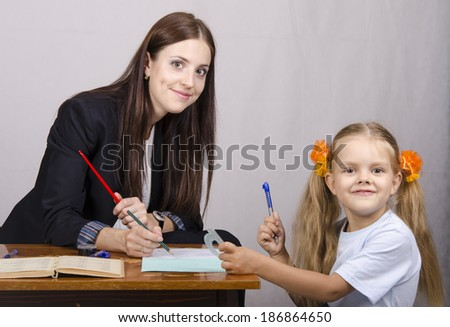 At the table sat a teacher and a student. Student teaches lessons, the teacher helps.
