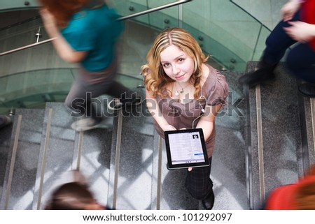 At the university/college - Students rushing up and down a busy stairway - confident pretty young female student looking upwards while using her tablet computer(color toned image) - stock photo