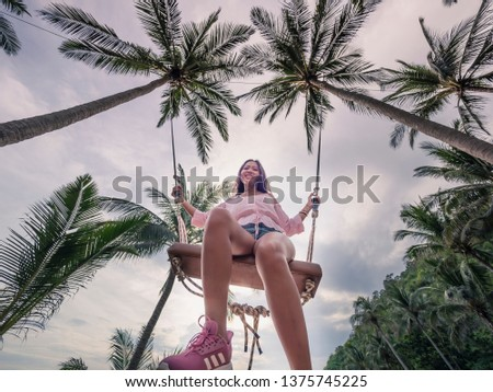 At water beach in phuket Thailand. On 06/05/2018 Woman is relaxing and playing swing with sunshine and beautiful beach #1375745225