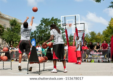 ATHENS, GA - AUGUST 24:  A young man takes part in the three-point shot contest, which was part of a 3-on-3 basketball tournament held on the streets of Athens, on August 24, 2013 in Athens, GA.