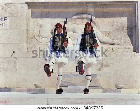 ATHENS, GREECE - AUGUST 15: Evzones (presidential guards) watches over the monument of the Unknown Soldier in front of the Greek Parliament Building at Syntagma Square,August 15, 2009 Athens,Greece.