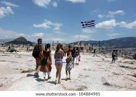 ATHENS, GREECE - JUNE 26: Tourists in famous old city Acropolis on June 26, 2011 in Athens, Greece. Its construction began in 447 BC in the Athenian Empire. It was completed in 438 BC
