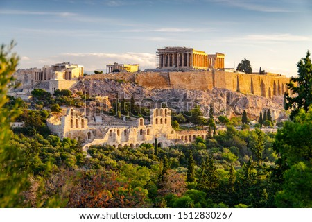 ATHENS, GREECE – NOVEMBER 4, 2018: Famous Athens landmark Acropolis and the Odeon of Herodes Atticus, Herodeion, just after the sunrise. View from Filopappou Hill with lots of olive trees and conifers