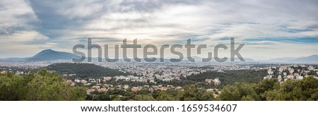 Athens Greece panorama. Aerial view of city from Penteli mount, profitis Ilias hill, cloudy sky. Panoramic view of Attica landscape, mountains and hills, parks, residential districts and the sea Foto stock ©