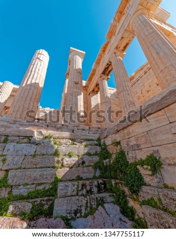Athens Greece, Propylaea columns and stairways of Acropolis entrance under vibrant blue sky, extreme perspective #1347755117