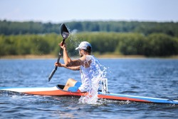 athlete at rowing kayak on lake during competition. spray of water under  paddle