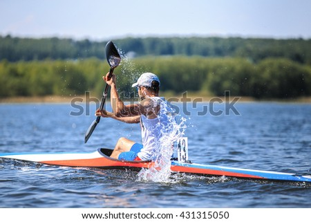 athlete at rowing kayak on lake during competition. spray of water under  paddle #431315050