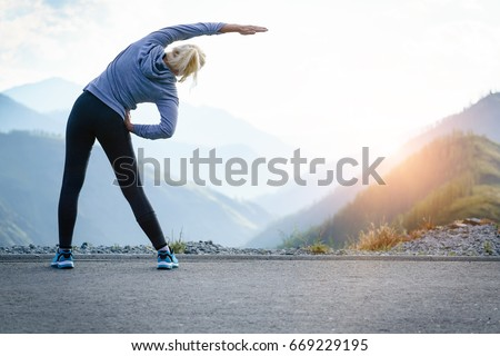 Athlete at the top of the mountain doing workout