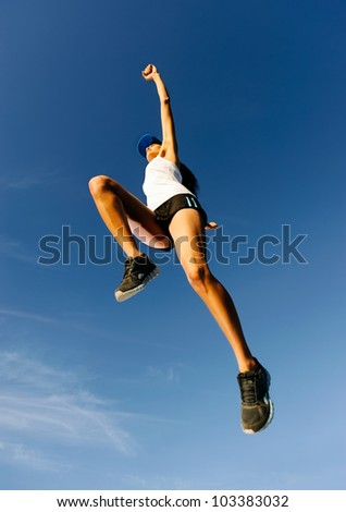 Athlete celebrating jumping and leaping against a blue sky. healthy wellness fitness woman in air - stock photo