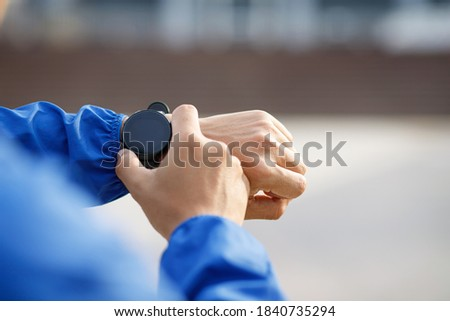 Photo of  Athlete checking his wrist watch race timer running ready on practice outdoor field.