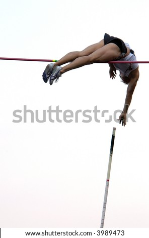 Athlete clearing the bar during a pole vault event in Prague, Czech Republic.