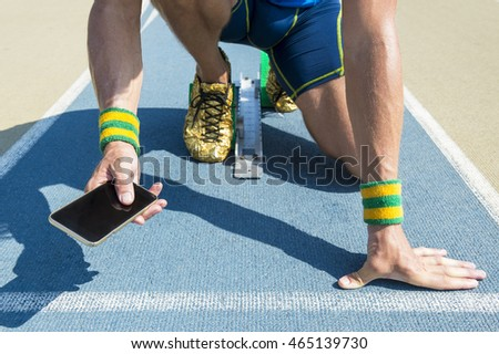 3861829ebfcd54 Athlete crouching at the starting line of a running track wearing Brazil  colors wristbands checking his