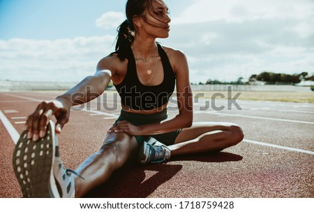 Athlete doing stretching exercises on running track. Woman runner stretching leg muscles by touching his shoes and looking away. Foto stock ©