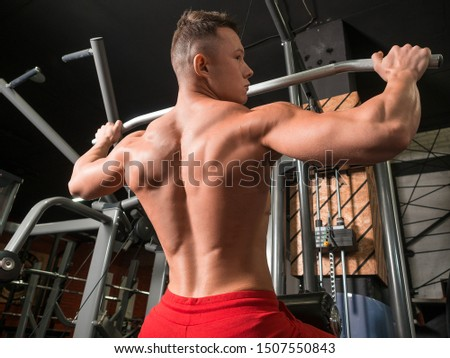 Athlete doing workouts on a back with power exercise machine in a gym club. Healthy lifestyle and motivation concept.