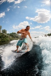 athlete handsome man surfer rides the river waves on the background of blue sky and beautiful clouds