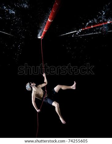 Athlete hanging on rope-hiking-isolated on black background