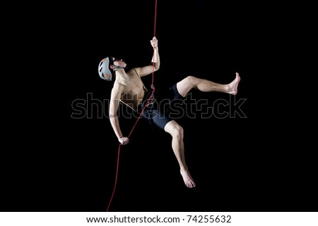 Athlete hanging on rope-hiking-isolated on black background