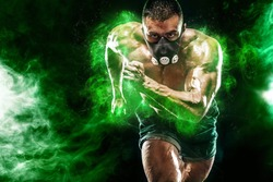 Athlete in green energy lights. Strong athletic man sprinter in training mask, running, fitness and sport motivation. Runner concept with copy space. Dynamic movement.