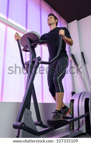 Athlete in gym elliptical machine. Man training hearth with cardio exercising in treadmill. Sportsman working out.