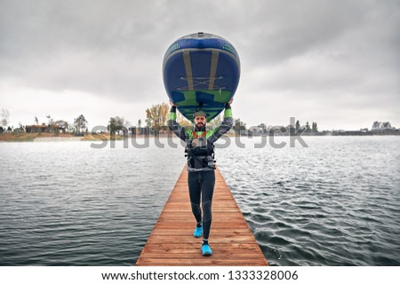 Athlete in wetsuit carries his paddleboard at wooden pier at the lake at cold weather against overcast sky  #1333328006