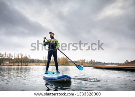 Athlete in wetsuit on paddleboard exploring the lake at cold weather against overcast sky  #1333328000