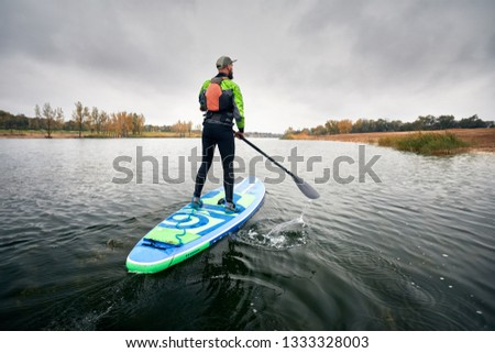 Athlete in wetsuit on paddleboard exploring the lake at cold weather against overcast sky  #1333328003
