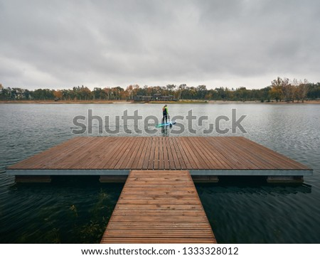 Athlete in wetsuit on paddleboard exploring the lake at cold weather against overcast sky  #1333328012