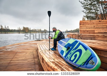 Athlete in wetsuit with paddle and surf sitting at wooden pier near the lake  #1333328009