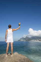 Athlete in white uniform standing with sport torch above Rio de Janeiro Brazil skyline at Ipanema Beach