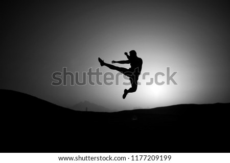 Athlete jump high with energy. Sportsman silhouette on sunset sky. Man training on natural landscape. Workout in summer dusk. Sport, wellness and bodycare concept. #1177209199