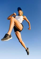 Athlete jumping shot from low angle with sky background