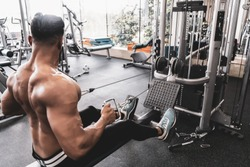 Athlete makes low cable pulley row seated in gym. Close back view