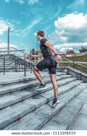 Athlete male athlete running in the summer in city on a morning run on the stairs, view from the back from the side, sportswear, motivation lifestyle active.