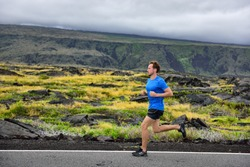 Athlete male runner running on mountain road. Running man jogging fast training cardio for marathon on countryside path in nature landscape, volcano background. Young Caucasian adult in his 20s.