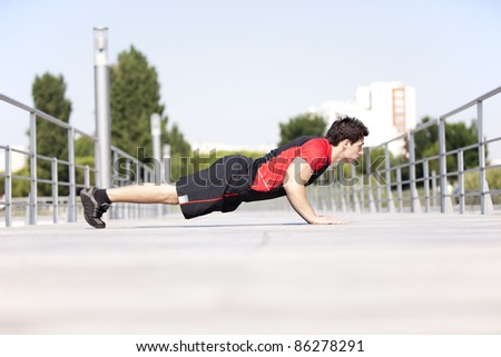 Athlete man at the city park making some push up