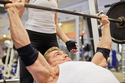 Athlete man does bench press from chest exercise in gym hall under supervision of female coach