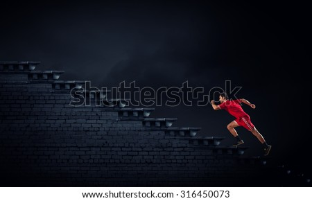 Athlete man in red sport wear running up staircase