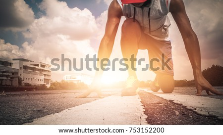 Athlete man in running pose on city street. Sport tight clothes. Bright sunset. sport man on starting position 20-30s