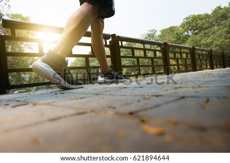 athlete man tired walks exercising in a park, workout concept