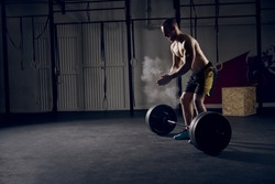 Athlete motivates screaming before barbells exercise at gym