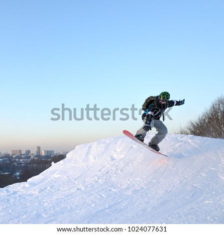 Athlete on a snowboard jumping from a springboard. Moscow, Russia - February 13, 2018 #1024077631