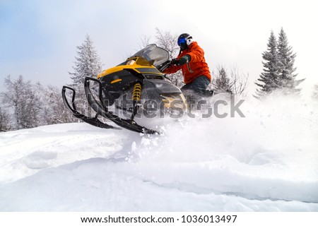 Athlete on a snowmobile moving in the winter forest in the mountains of the Southern Urals. - Shutterstock ID 1036013497