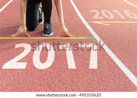 Athlete on starting line waiting for the start in running track with text 2017 year, Start to new year #490310620