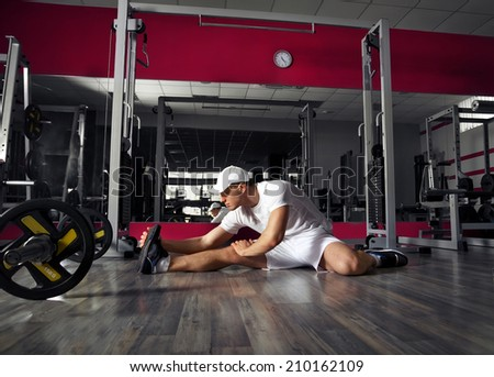 Athlete performs exercise in sport gym hall