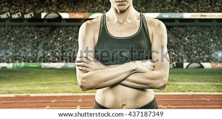 Athlete posing with arms crossed against view of a stadium